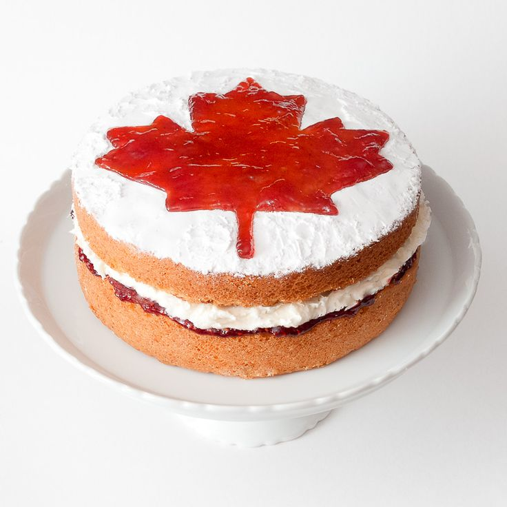 A classic Victoria sponge sandwich topped with a maple leaf to celebrate the Victoria Day holiday in Canada.