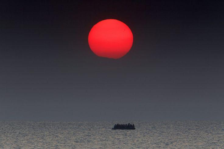 Alors que le soleil se lève, un canot surpeuplé de réfugiés syriens dérive dans la mer Egée. Son moteur est tombé en panne lors du voyage de la côte turque vers l'île grecque de Kos. Un bateau des Garde-côtes grecs a répondu à des signaux de détresse et est arrivé sur les lieux pour leur porter assistance. 11 Août 2015 - REUTERS / Yannis Behrakis