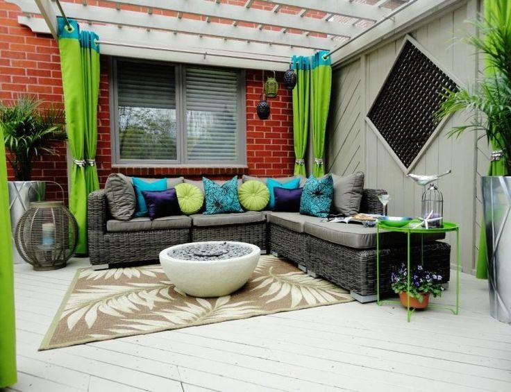 coussins multicolores et rideaux extérieur en bleu et vert sur la terrasse