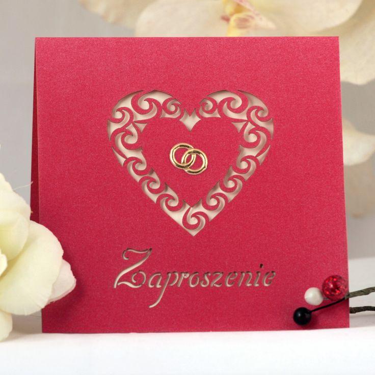 Zaproszenie ślubne wycinane laserowo z motywem serca i złotymi obrączkami w środku.