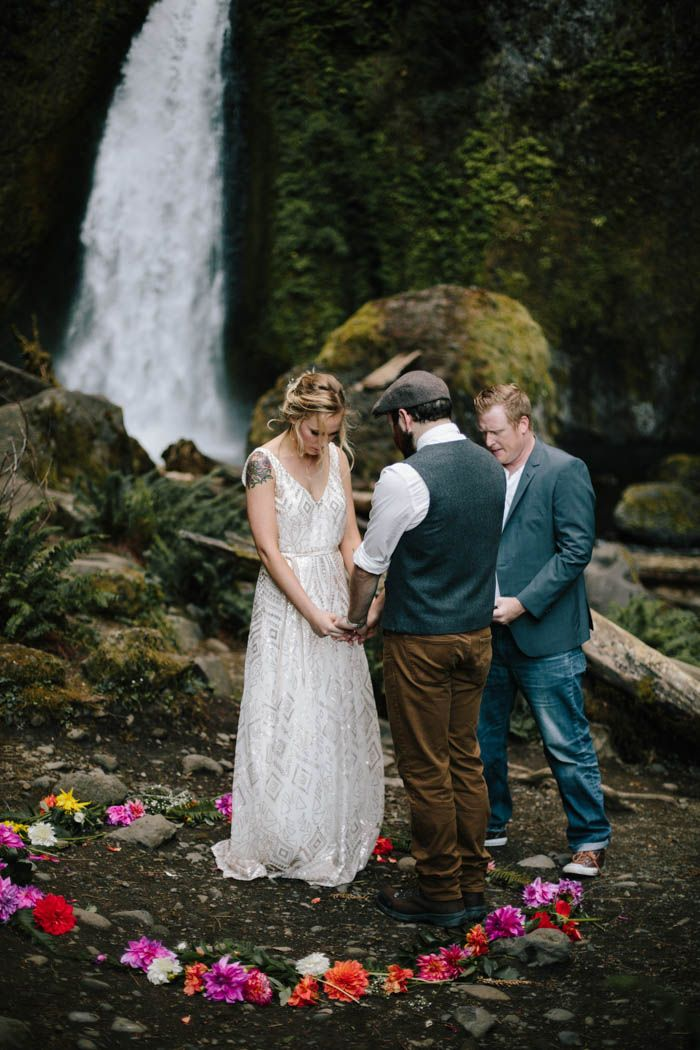 A waterfall, a ring of flowers, and a secluded spot in the middle of the woods = wedding ceremony goals | Image by Abby Tohline Photography Co.