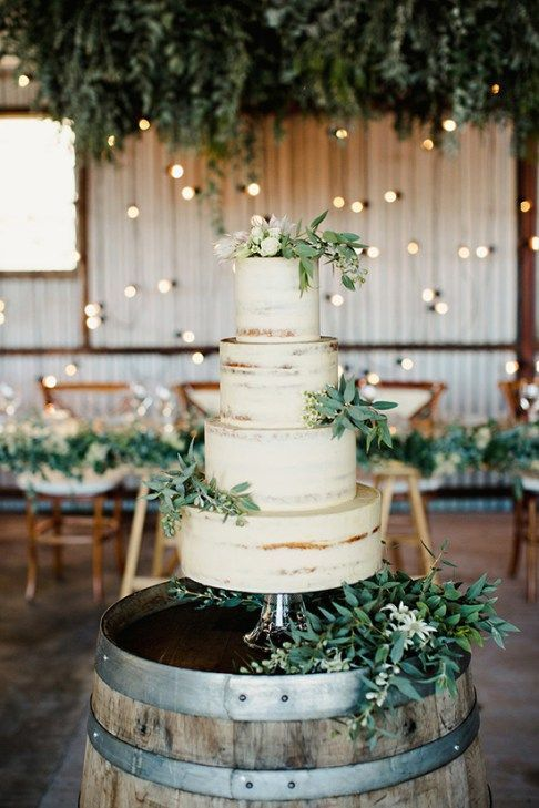 Asymmetrical clusters of parvifolia eucalyptus, bay laurel, and seeded eucalyptus on the cake tiers