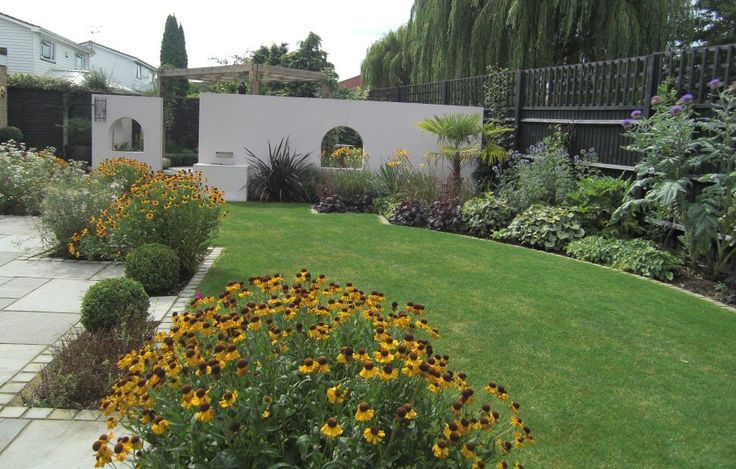 A wide shallow contemporary garden design in Windsor, Berkshire with a walled courtyard screened with a a chunky pergola.  This garden also has large patio and structural planting.  Designed by Linsey Evans GArden Design www.linseysgardens.com.