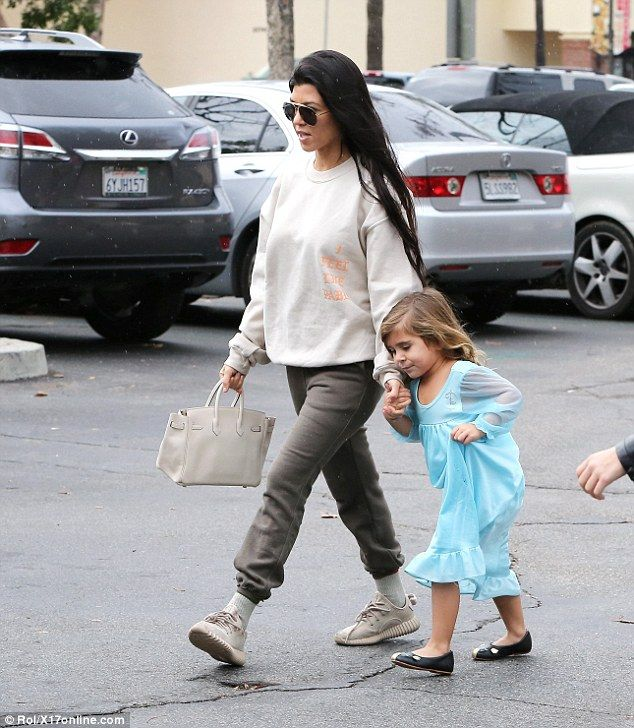 Out and about: Kourtney Kardashian, 37, held four-year-old daughter Penelope's hand as the family stepped out in their native Calabasas for a bite on Friday