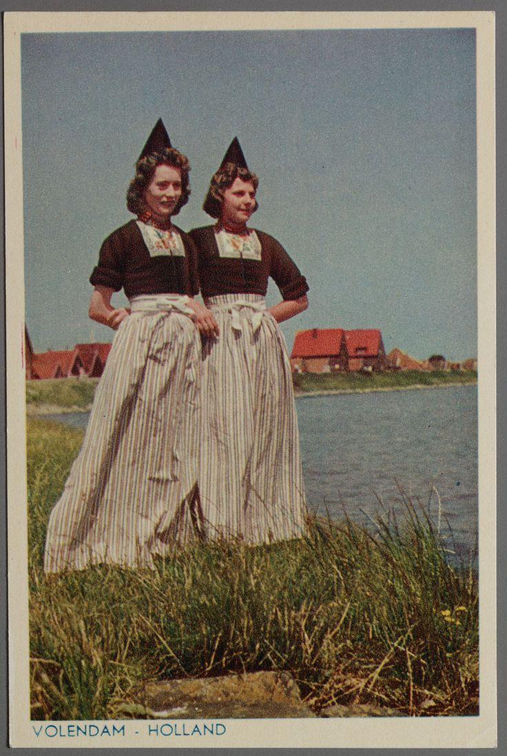 Twee jonge Volendammer vrouwen in klederdracht: Huibje Buys (Schaap) en rechts Maartje van Vlaanderen (Pan), gekleed in ondermuts, kletje en gestreept schort. 1950-1970 #NoordHolland #Volendam