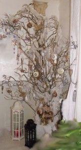 Une nouvelle forme de sapin.J'ai remplacée mon sapin par des branches de lilas, décoré de boules, de plumes et de strass, un père noël est posé à son pied.