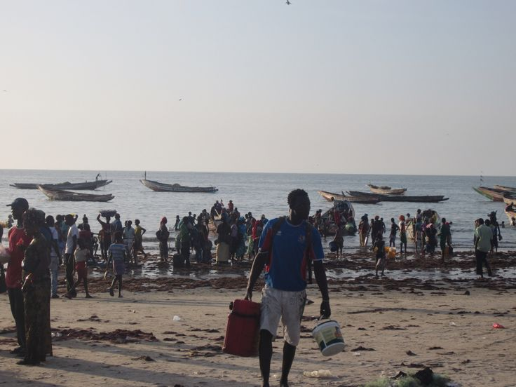 Op het strand van Tanji is het onwijs druk als de vissersbootjes binnenkomen. Veel mensen willen helpen om wat geld te kunnen verdienen.