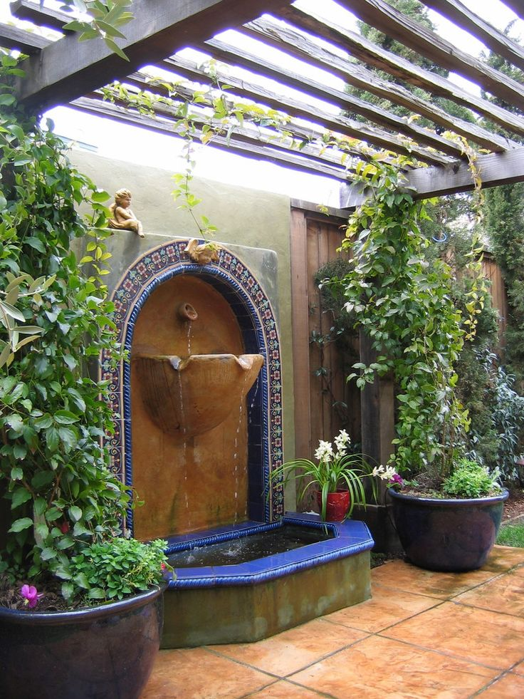 Mediterranean garden fountain with blue mosaic tiles and terracotta paving