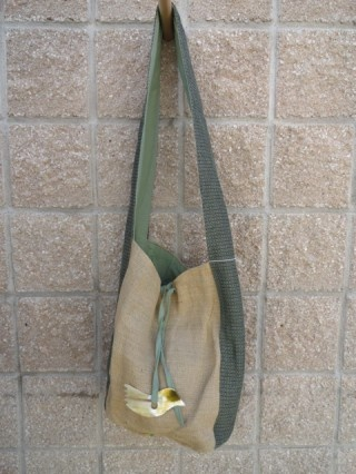 Chelsea–Burlap  $40  This is a burlap purse with 1 long fabric strap and it is fabric lined. The bag is approximately 16×12. There is an ornamental piece made out of horn on each bag! It ties shut. There are 2 smaller pockets inside perfect for your cell phone or keys.