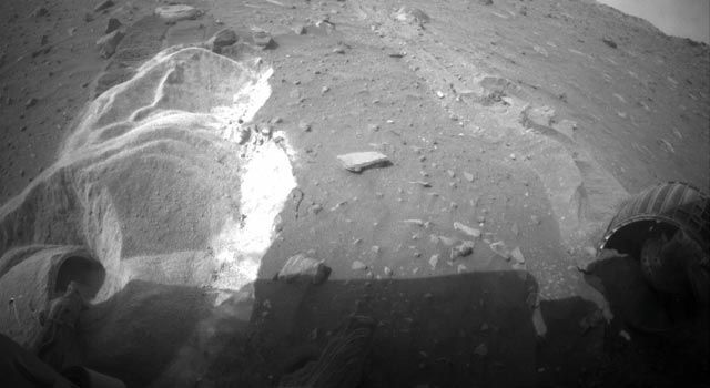 """Spirit Rover Stuck in """"Difficult Situation"""" -- In the past week, the digging-in of Spirit's wheels has raised concerns that the rover's belly pan could now be low enough to contact rocks underneath the chassis, which would make getting out of the situation more difficult. The right-front wheel on Spirit stopped working three years ago. Driving with just five powered wheels while dragging or pushing an immobile wheel adds to the challenge of the situation."""