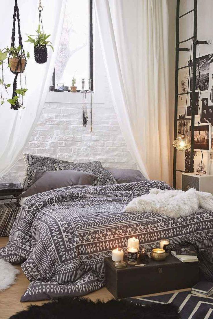 chambre à coucher de style bohème avec couette grise à motifs blancs, rideaux en blanc et beige et porte-plantes en macramé