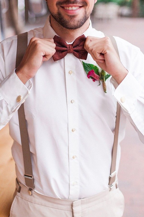 A deep burgundy bowtie mixed with a green boutonnière - Enchanted Empire