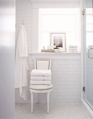 In the master bath, a Swedish-style chair covered in white vinyl substitutes for a towel bar. Walls are tiled from floor to ceiling in beveled-edge subway tile.