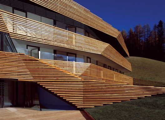 Hotel Strata / PLASMA Studio. Located on a steep hillside in the Italian Dolomites this new-built hotel has been developed as the interweaving of the free-flowing topography- indexed and organized by series of timber strips- and the serial sequence of appartment units perpendicular to it.