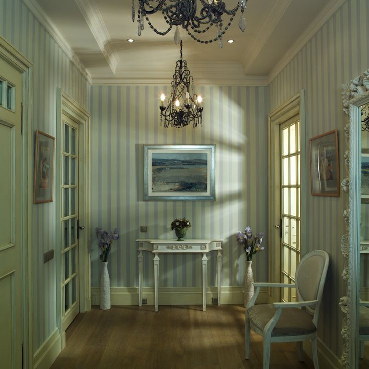 Classic interior design with provence style motives. Light colors, vertical stripes, classic white furniture and doors with craquelures, the mirror with a sophisticated frame, art deco chandelier and lilac flowers.