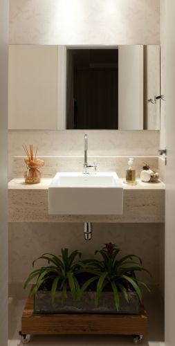 O mármore travertino foi usado na bancada que sustenta a cuba de semi-encaixe branca quadrada. Sob ela, ao invés de um gabinete, um vaso de plantas foi colocado sobre uma plataforma de madeira com rodízios. O projeto é da designer de interiores Iara Santos