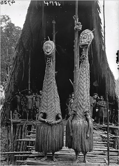 Papua New Guinea   Masked dancers in front of the men's longhouse at Tovei village. Urama Island, Gulf Province.  June 1921.   ©Frank Hurley, courtesy Australian Museum.