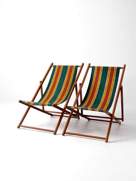A pair of vintage deck chairs circa 1940s. The wood frame chairs feature green canvas seats with orange, red, and white stripes. The chairs have three seating positions with a hooked back bar for adjustment. • pair (2) deck chairs • original green canvas ticking seats • wood frame  CONDITION In good condition with wear consistent with age and use. There is a repair stitch and patch on one chair near the bottom crossbar. MEASUREMENTS Folded: 49 x 22.5 x 1.5 Tall: 36 H x 34.5 D x 22 W Middle…