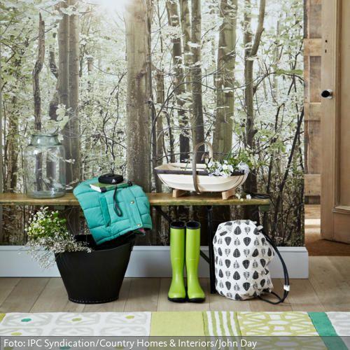Durch die Fototapete mit Waldmotiv wird dieser Flur zur grünen Oase. Eine Klappbank aus Holz und der grüne Teppich komplettieren den natürlichen Look.