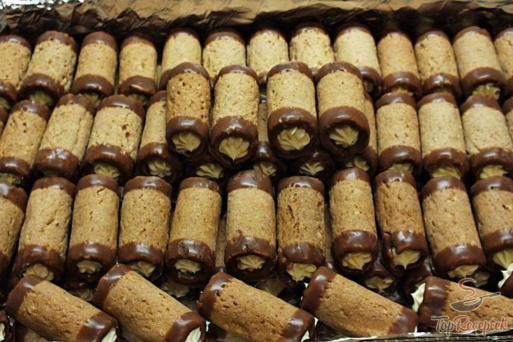 A mézes roló mellett a karácsonyi diós roló is nagy népszerűségnek örvend. Igazság szerint mind a kettő elkészítem (és nem kis mennyiségben), mert nem tudom eldönteni, melyik a finomabb, és mindkettő nagyon ízlik. A mostani diós rudakat lágy vajas krémmel töltöttem, és persze az elengedhetetlen csokoládéval díszítettem. Ha van egy kis konyhai rutinunk, akkor a tészta elkészítése és felcsavarása a sütőformára nem nagy munka, és nagyon gyorsan megy.