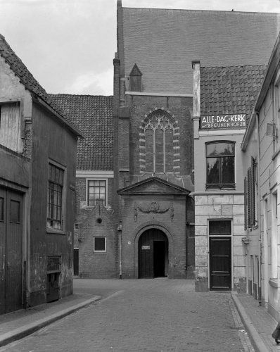 Gezicht op de Lange Begijnestraat in Haarlem, met op de achtergrond de poort / ingang en een gedeelte van de Waalse Kerk. Op het dak van het huisje rechts in beeld staat te lezen
