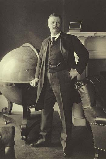 Theodore Roosevelt, full-length portrait, standing beside large globe, facing…