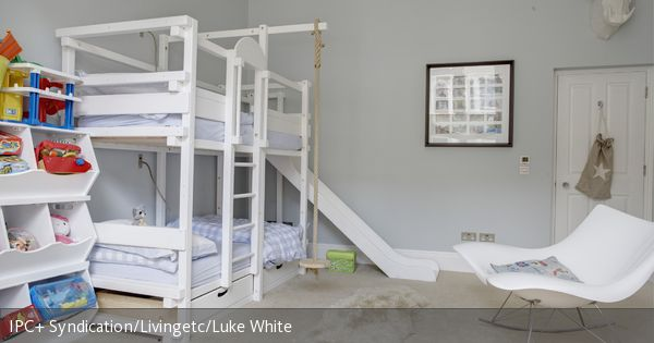 Das Hochbett mit Rutsche und Schaukel macht das Kinderzimmer zum Indoor-Spielplatz. Der helle Teppich mit dem Lammfell und die hellgrauen Wände lassen den Raum gemütlich und warm erscheinen.