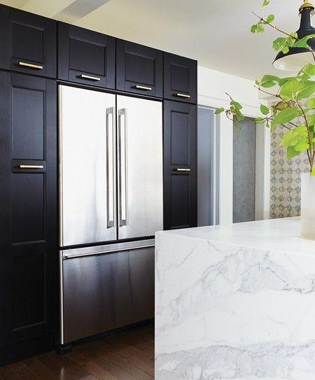 Black kitchen cabinets. Brass hardware. Stainless steel refrigerator. Marble island.