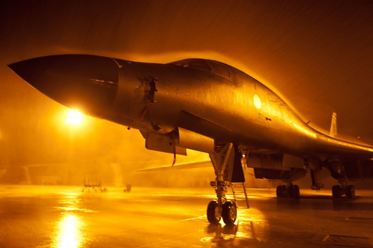 Lights in the aircraft parking area cast an eerie glow around a B-1 bomber standing at the ready during a summer rainstorm at Ellsworth Air Force Base, S.D., July 24, 2012. Ellsworth is home to 28 B-1 bombers and two of the Air Force's three B-1 combat squadrons.