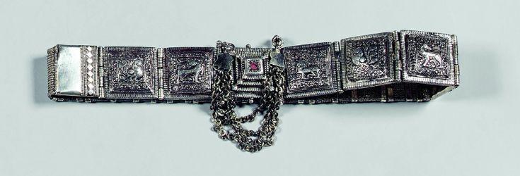 Lot : Importante ceinture en argent composée de plaques articulées sur.lesquelles se trouvent un paon ,un cheval et des fleurs ,le motif central représente le mont Meru axe du monde dans la mythologie hindou .. | Dans la vente Fashion Tribal Week à Eve Enchères