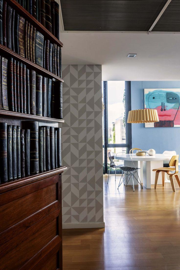 Puerta que simula una biblioteca: la entrada a un departamento en el edificio Malabia, del Studio ai. En el living comedor, azul cerúleo o calipso con matices grises en combinación con el marrón de la madera.