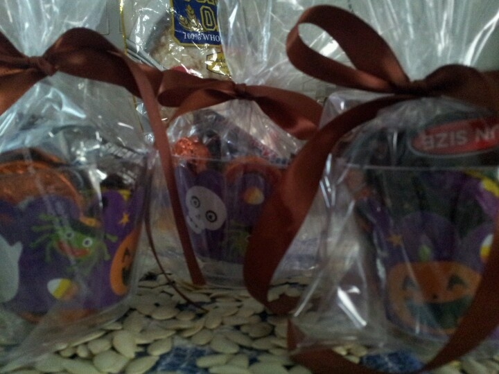 Just made these little treats. Clear plastic cup, cupcake liner, fill with candy, place inside of clear treat bag, tie with ribbon and love!