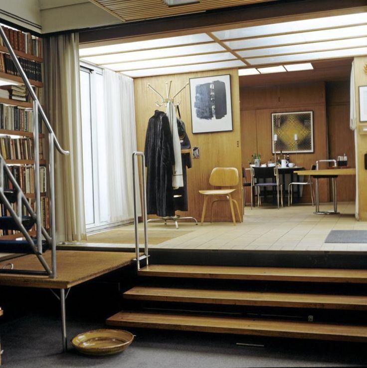 """RÅ MODERNISME: Fra stuen går du tre trinn opp til hall og kjøkken. Store overlyspaneler i taket og mahognifiner på veggene. Helt fra starten i 1954 hadde dette huset varmeanlegg i alle gulv. """"Plywood""""-stolen er et minne fra et opphold ekteparet Prytz/Korsmo hadde i Charles og Ray Eames hjem i California. © FOTO: Sølvi dos Santos"""