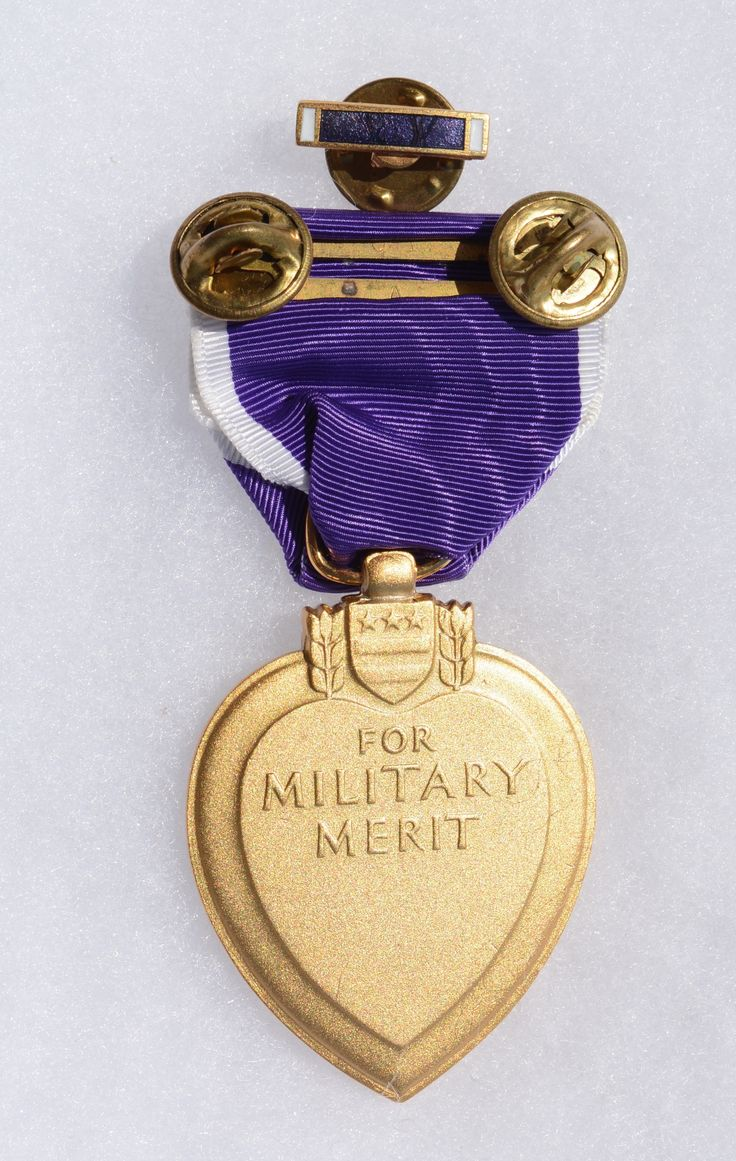 Backside view of a full size Purple Heart medal, which is a United States military decoration awarded in the name of the President to those wounded or killed, while serving, on or after April 5, 1917, with the U.S. military. With its forerunner, the Badge of Military Merit, which took the form of a heart made of purple cloth, the Purple Heart is the oldest military award still given to U.S. military members. This version features a double 'pin back' clutch with a ribbon lapel bar.