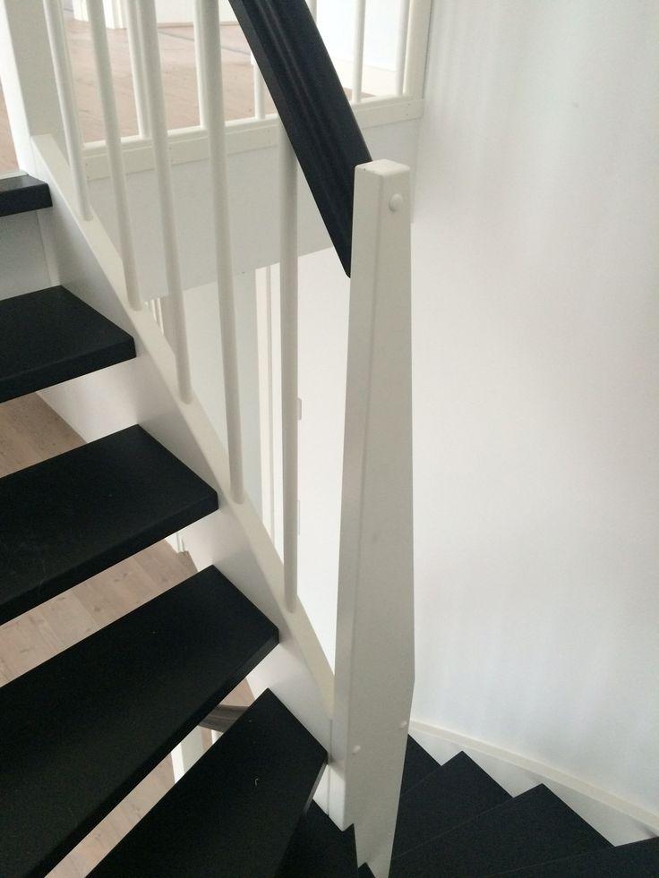 Vitmålad u-trappa med svartlackerade steg och handledare.