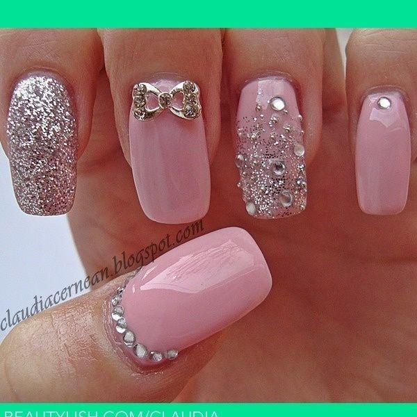 Estilosas uñas en color rosa pastel, algunas de ellas adornadas con brillos plateados, otras con perlas cristalinas y un hermoso lazo.