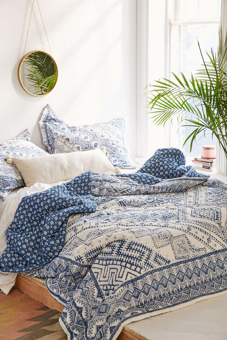 Magical Thinking Echo Graphic Quilt - Urban Outfitters blue pattern bedding with white sheets, wooden bedframe, very light gray/white walls