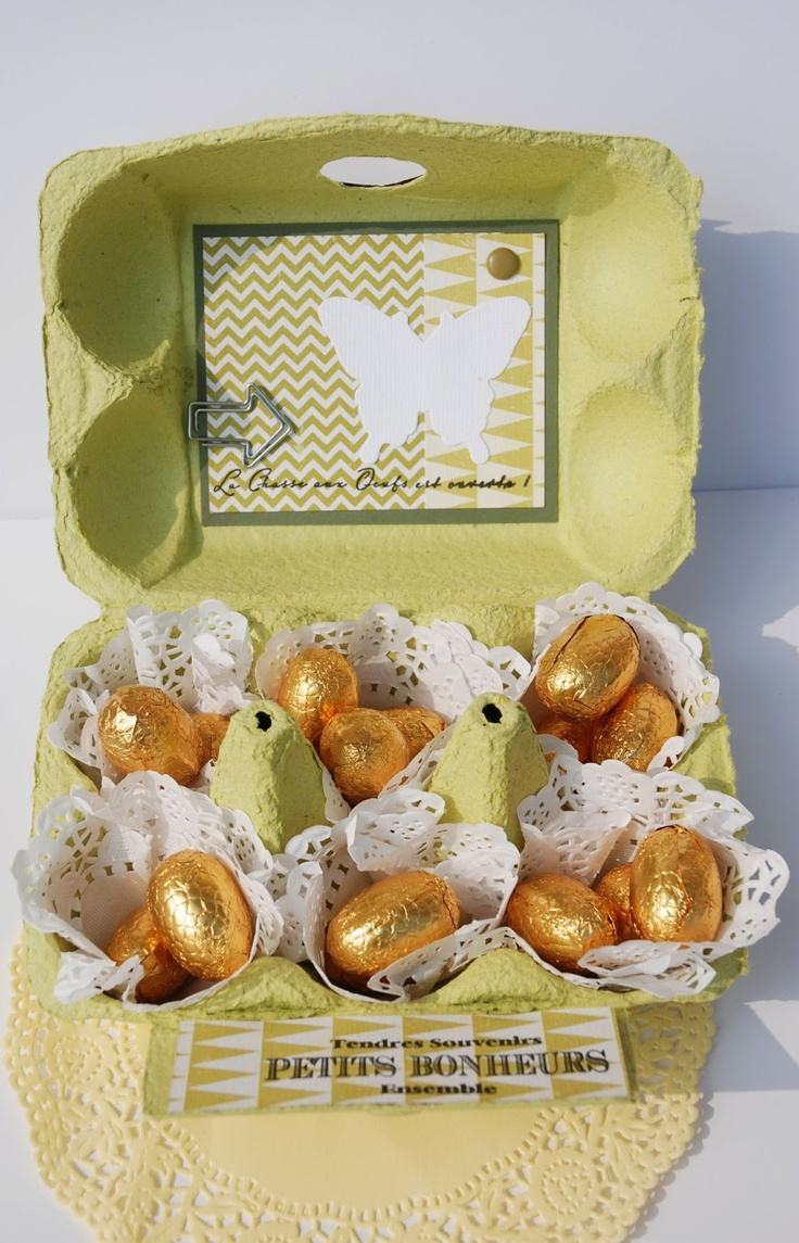 Paper doilies underneath chocolate eggs in egg carton.
