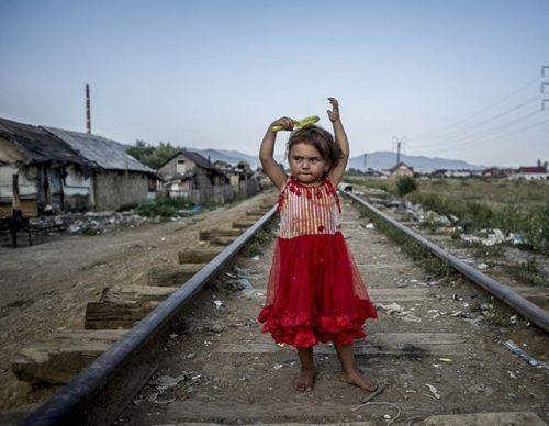 Nikon 100th Anniversary: 100 anni di storie Questa foto è stata scattata da András D. Hajdú fotografo Nikon nella baraccopoli di Baia Mare. Raffigura la povertà del luogo con una bambina dal vestito rosso che cerca di spazzolarsi i capelli con un pettine privo di denti. András Hajdú D. con #D3  AF-S Zoom NIKKOR 17-35mm f/2.8D IF-ED #Nikon100 #nikonitalia #iamdifferent #nikoncentoanni #bambina #povertà #baraccopoli #pettinarsi #binari #rosso #pettine #baiamare #foto #fotografia via Nikon on…
