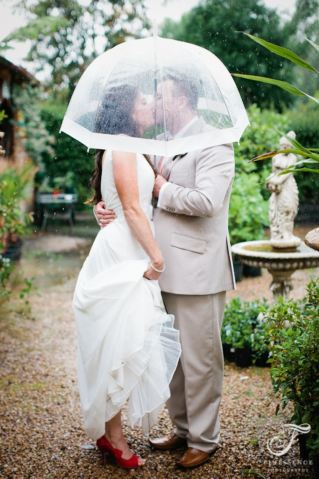 Our bride and groom sheltered under a see through umbrella // Melbourne Wedding photography by Finessence // www.finessence.com.au
