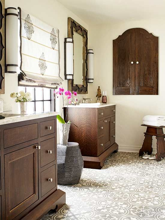 Large-format decorative tiles span the length of this master bath to provide style underfoot. The swirling pattern repeats on classic Roman shades, which incorporate the chocolaty hue of the neutral bathroom's furniture. Pops of bright white, including marble countertops and European-style sconces, balance a dark vanity and built-in medicine cabinet./