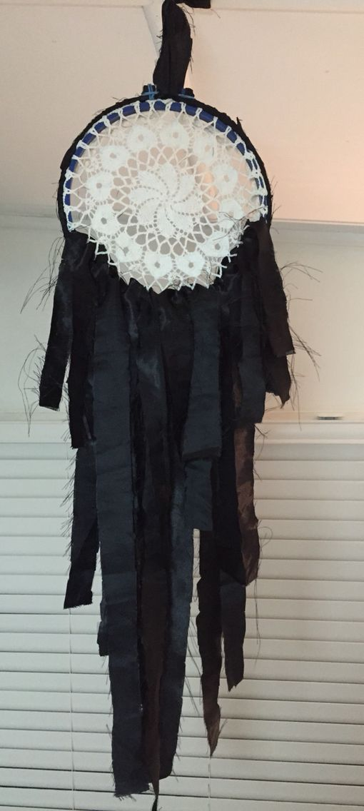 Boho dream catcher. Stitching hoop (outer ring wrapped in strips of material), doily placed over inner ring and hoop put back together again. Strips of material of varying lengths fed through lower holes of doily.