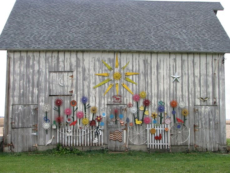 Old barn decorated with painted farming tools.  | Wallace Gardens