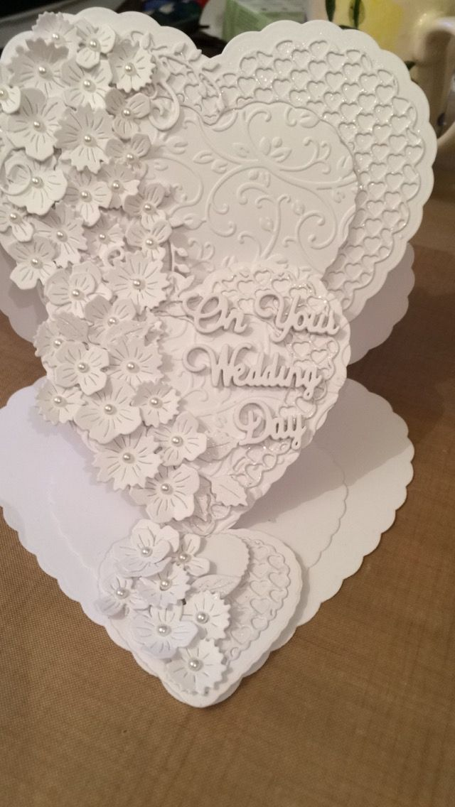 """White on White wedding card commission. An easel card using assorted heart dies, some embossed, Tattered Lace flower die - but can't remember which one  - text dies from Crafter's Companion """"Die'Sire"""" range and finished with tiny pearls"""