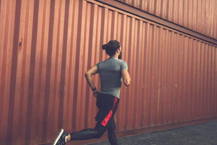 Backside of an athletic man, who is running through an industrial area.
