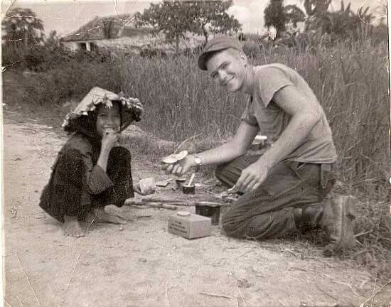 """Donald Clark 09-19-1943 to 11-02-2013 RIP . This is Donald in Vietnam sharing his food rations with a Vietnamese child. He was in the Central Highlands about 30 miles from """"An Khe'"""", 1st Cavalry base camp. - Andrew Clark"""
