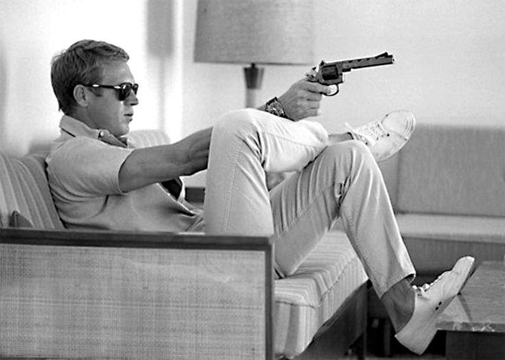 Steve McQueen. Short pants, white sneakers. Classic polo, classic sunglasses, classic watch, classic handgun.
