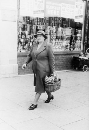 Ministry of Information Photo Division Photographer -- A housewife with a shopping basket full of bananas after a visit to the Co-Op store on Westhorne Avenue, Eltham in London, 1940.