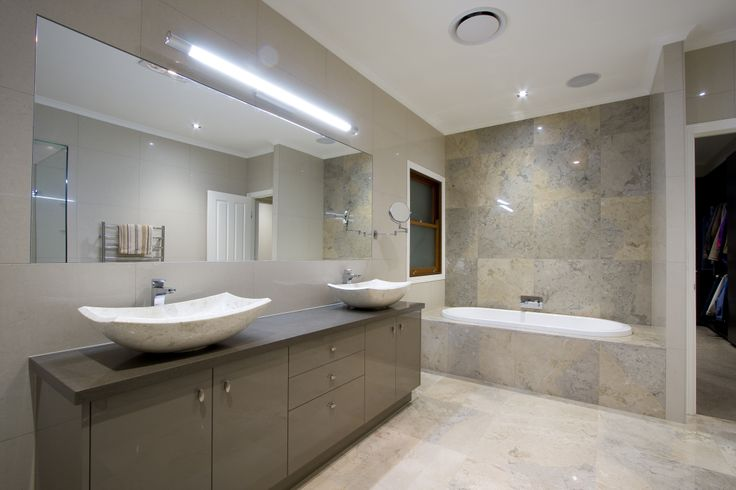 The ensuite is a work of art. Travertine and marble tiling up to the cornice is complemented by a large frameless glass shower, a bath with a view, heated towel rails, and of course a lovely double vanity unit.