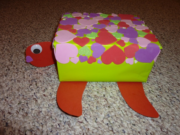 "Turtle Valentine box 2011. Small shoe box covered in green wrapping paper, cardstock for head tail and flippers, foam sticky hearts for the ""shell,"" and google eyes."